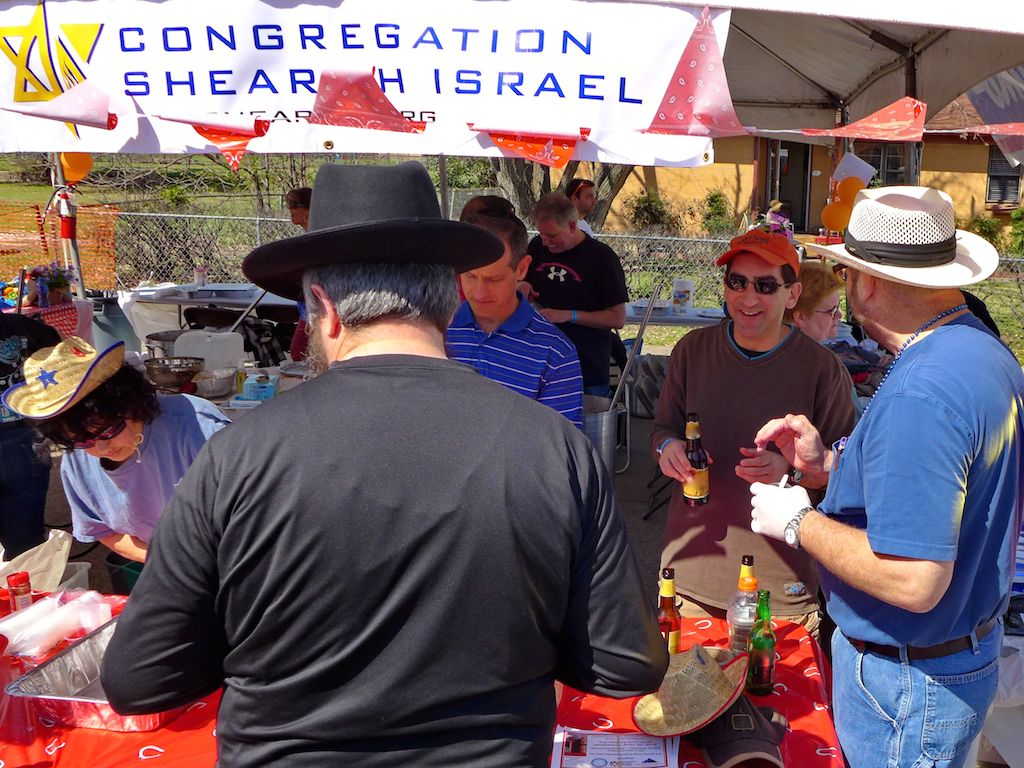 a crowd gathers at a team booth at dallas kosher chili cook-off