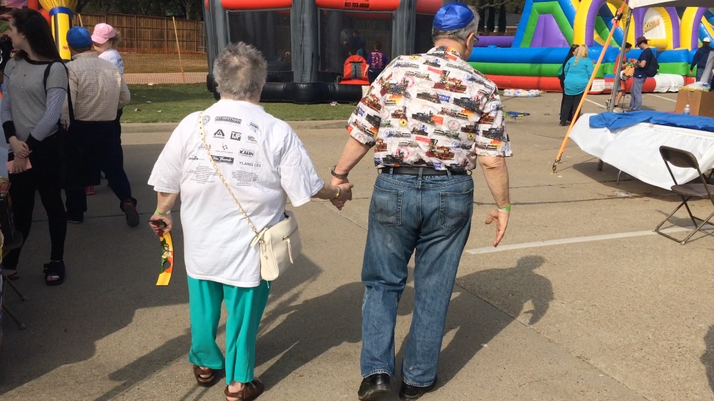 couple stroll through the cook-off holding hands.
