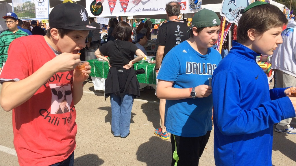 three boys walk and eat chili samples at the dallas kosher chili cook-off.